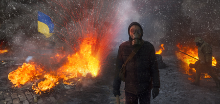 radical: Radical Protestant in the mask represents the protesters against the authorities among the burning of the capital of the European quarter. Burning rubber tires wheel of fire smoke soot street fighting