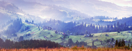 sunrise, the suns rays illuminate the beautiful panorama of the Carpathian village against backdrop of scenic mountains, where the highlanders live Hutsul. Wild forests, fields pastures