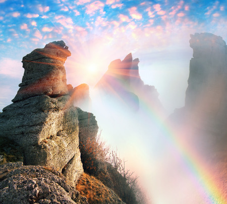 Rocks teeth on Demerdzhi - famous tourist Crimea. Sunrise over ancient rocks of the Black Sea in the background fog after heavy rain storms and rain is very beautiful for climbers
