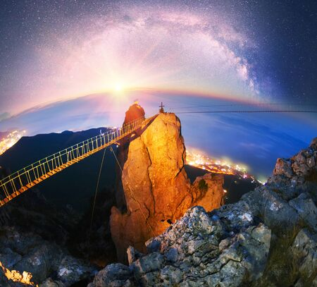 Rocks teeth above Yalta - famous tourist Crimea. Milky Way stars and galaxies lit at the ancient rocks of the Black Sea On the left is the famous historic a funicular for tourists Stock Photo