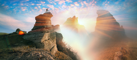 downhill skiing: At sunrise in Crimea bold mountain bike MTB racer wins top for downhill skiing in the fog. sea mist is very strong and beautiful against the backdrop of the ancient rocks of fantastic fairy
