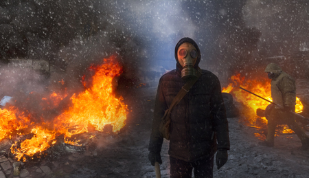 Radical Protestant in the mask represents the protesters against the authorities among the burning of the capital of the European quarter. Burning rubber tires wheel of fire smoke soot street fighting Stock Photo