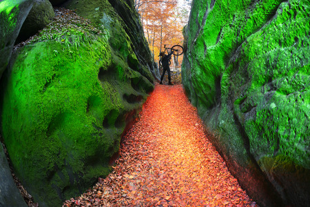 worshiped: The reserve Dovbush Rocks near Bubnyshche - pagan temple, an ancient Christian monastery, fortification, worshiped gods wildlife Carpathians. Athlete rises from the valley to the route Stock Photo