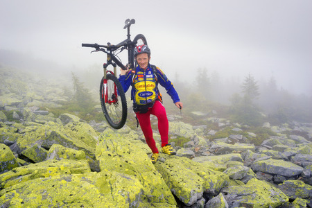 conquer: Ukraine, Vorohta- June 15, 2016: The climber with a mountain bike and conquer peaks Hamster Synyak in Gorgany, Carpathian Mountains on the background of wild mountain landscape Stock Photo