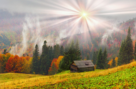 In the Carpathians, golden autumn often turns into snow, and then again warm, sunny days. Against the background of high mountain ranges of the forest with a beautiful sun shining over the hut Stock Photo