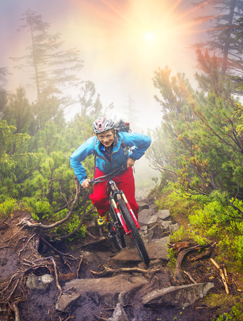 The climber with a mountain bike and conquer peaks Hamster Synyak in Gorgany, Carpathian Mountains on the background of wild mountain landscape Ukraine, Vorohta
