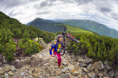 Ukraine, Vorohta- June 15, 2016: The climber with a mountain bike and conquer peaks Hamster Synyak in Gorgany, Carpathian Mountains on the background of wild mountain landscape Stock Photo