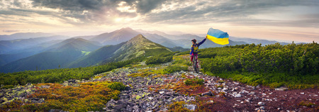 Ukraine, Vorohta- June 16, 2016: The climber with a mountain bike and conquer peaks Hamster Synyak in Gorgany with yellow-blue national flag of Ukraine on the background of wild nature