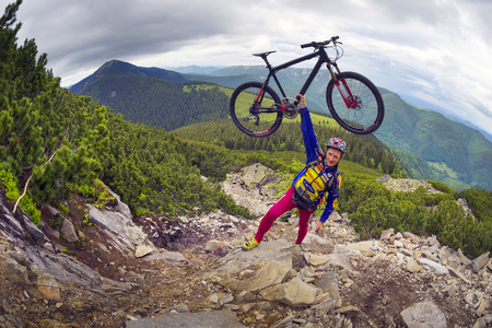 vorohta: Ukraine, Vorohta- June 15, 2016: The climber with a mountain bike and conquer peaks Hamster Synyak in Gorgany, Carpathian Mountains on the background of wild mountain landscape Stock Photo