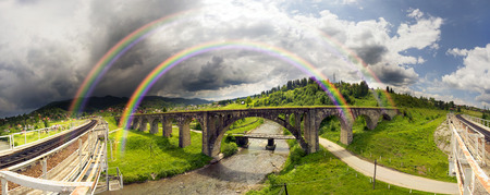 vorohta: The Alpine village of Vorokhta, Vorohta is a series of old ancient Austrian bridges with monumental classical arches. Thunderstorm and rain - create a beautiful rainbow over the mountains
