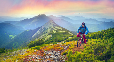 vorohta: The climber with a mountain bike and conquer peaks Hamster Synyak in Gorgany, Carpathian Mountains on the background of wild mountain landscape Ukraine, Vorohta