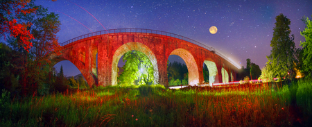Alpine village of Vorokhta, Vorohta is a series of old ancient Austrian bridges with monumental classical arches. At night with illumination against the backdrop of the beautiful starry sky