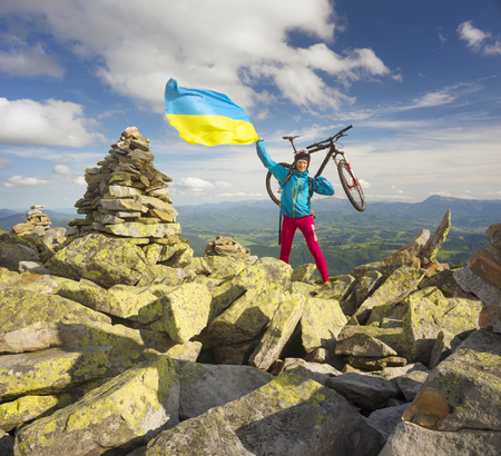 conquer: Ukraine, Vorohta- June 16, 2016: The climber with a mountain bike and conquer peaks Hamster Synyak in Gorgany with yellow-blue national flag of Ukraine on the background of wild nature