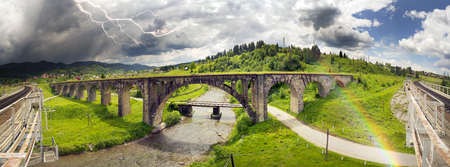 The Alpine village of Vorokhta, Vorohta is a series of old ancient Austrian bridges with monumental classical arches. Thunderstorm and rain - create a beautiful rainbow over the mountains