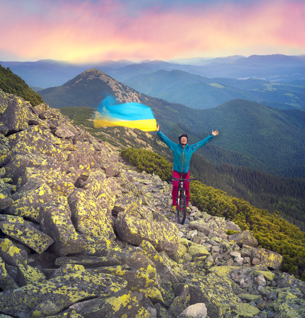 The climber with a mountain bike and conquer peaks Hamster Synyak in Gorgany with yellow-blue national flag of Ukraine on the background of wild nature Ukraine, Vorohta