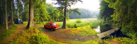 Ukraine, Verhovina- August 15, 2015: Fog after the rain covered mountain lake Ukrainian Carpathian Eye shore is covered with pine trees, where tent tourists and old Soviet car of local residents campers Stock Photo