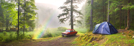 """Fog after the rain covered mountain lake Ukrainian """"Carpathian Eye"""" shore is covered with pine trees, where stoyat tent tourists and old Soviet car of local residents campers Ukraine, Verhovina"""