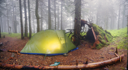 Ukraine, Vorohta- June 3, 2016: rain mist rider on a mountain bike prepares for spending the night in a tent near the old hut of moss in the wild alpine spruce forest among the windbreaks
