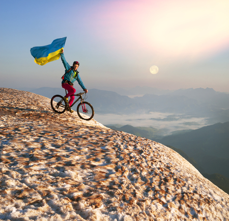 Racer bicycle on top of the highest peaks of the Carpathians Hoverla and Ukraine among the snow against the backdrop of mountain ranges and peaks in the glow of dawn greets the new day Stock Photo