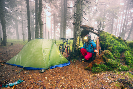 rain mist rider on a mountain bike prepares for spending the night in a tent near the old hut of moss in the wild alpine spruce forest among the windbreaks Ukraine, Vorohta Stock Photo