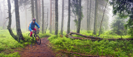 Ukraine, Vorohta- June 3, 2016: rain mist rider on a mountain bike overcome challenging tracks in the wild alpine forest, among rocks and windbreaks in the Carpathian marathon for off-road trails