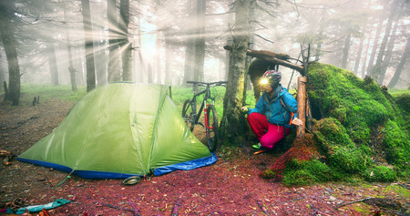 rain mist rider on a mountain bike prepares for spending the night in a tent near the old hut of moss in the wild alpine spruce forest among the windbreaks Ukraine Carpathians, Vorohta Stock Photo