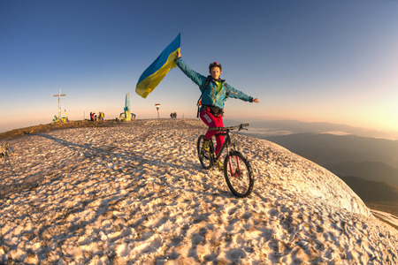 racer flag: Ukraine, Rakhiv - May 29, 2016: Racer bicycle on top of the highest peaks of the Carpathians Hoverla and Ukraine among the snow against the backdrop of mountain ranges and peaks in the glow of dawn greets the new day Editorial