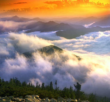 after a rain on a background of fog Ukrainian mountain ridges. Panoramic views from the top of the Hamster, which sleeps Ukrainian tourists for beautiful panoramas Carpathians dawn