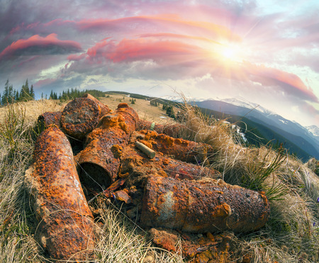 battles: Sleeves shells at the site of the old trenches of the First World War battles. Rusty metal, brass sleeve from a rifle on a background of the spring and the Carpathians mountains Hoverla, Ukraine