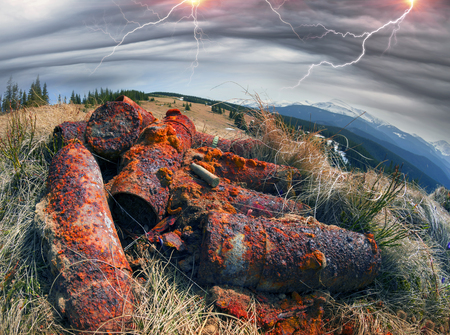 Sleeves shells at the site of the old trenches of the First World War battles. Rusty metal, brass sleeve from a rifle on a background of the spring and the Carpathians mountains Hoverla, Ukraine