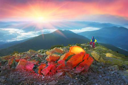 mountainbiking: Bivouac extreme riders MTB marathon on the Carpathian Gorgan through peaks and Synyak Hamster on a background of the night with beautiful valley of the Blue Ridge Mountains Stock Photo
