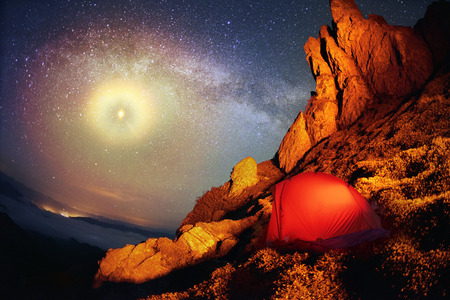 unearthly: Tent and the Milky Way. Artistic lighting unreal mountain scenery while rock climbing in the wild mountains provides a unique fantastic effect unearthly planets with fabulous landscapes of Mars