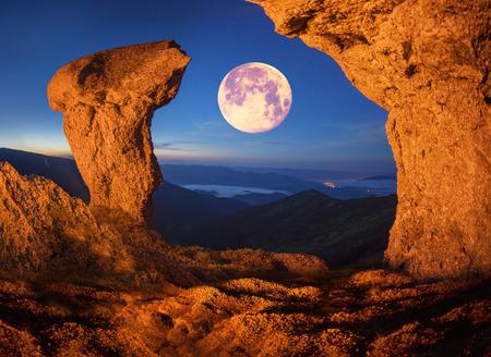 야생 산에서 암벽 등반을하는 동안 예술적 조명의 비현실적인 산의 경치는 독특한 환상적인 효과를 제공합니다 화성의 멋진 풍경을 가진 소름 끼치는