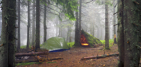 Rainy autumn landscape spruce forest in the rain at dawn with a tent. Modern tent and traditional hunters construction of sticks and moss in the misty distance, technology and tradition of tourism