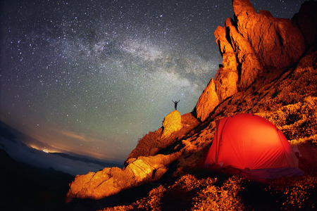 unreal: Tent and the Milky Way. Artistic lighting unreal mountain scenery while rock climbing in the wild mountains provides a unique fantastic effect unearthly planets with fabulous landscapes of Mars