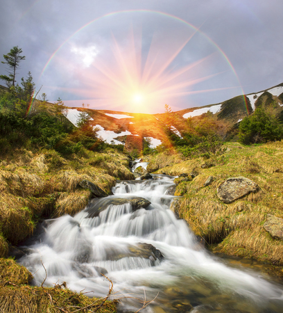 Falls breakers among melting snow under the peak of Hoverla, stormy clean water feeds the river Prut on the background of wild mountain slopes of the Carpathian Mountains. Stock Photo
