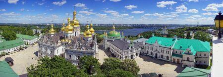 春のキエフ、寺院大聖堂キエフ ・ ペチェールシク大修道院の有名な鐘楼のパノラマ ビューの空気遠近法。栗咲く葉を飾る首都