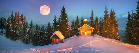 Old wooden church, located in the Carpathian Mountains on the ridge Chornohora, wild reserved place. Powerful flashlight helps illuminate the mountain slopes for unique photos