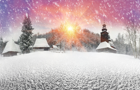 After sunset, the traditional Ukrainian village began snowfall and blizzards, snowdrifts pout and covered the roads and footpaths. Thick forest and gardens beautiful pattern on the background of sky Stock Photo