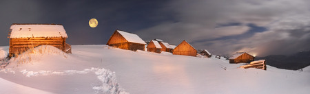 barns winter: Blizzard covered alpine fields shepherds in the Ukrainian Carpathians. Beautifully lit golden light barns and houses shepherds - cold winter and frost on the background of mountain peaks