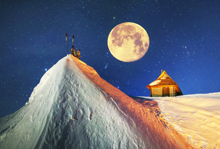 Beautiful wild Carpathian ridge - Montenegro, on the background of a powerful lantern-lit building - a refuge from snow bricks protecting tent extreme sportsmen from wind and frost