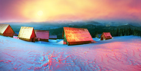 covered fields: Blizzard covered alpine fields shepherds in the Ukrainian Carpathians. Beautifully lit golden light barns and houses shepherds - cold winter and frost on the background of mountain peaks