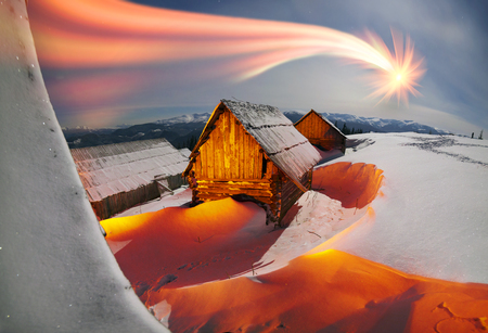 Blizzard covered alpine fields shepherds in the Ukrainian Carpathians. Beautifully lit golden light barns and houses shepherds - cold winter and frost on the background of mountain peaks