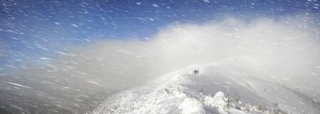 daring: bad weather brave and daring athletes overcome obstacles on the road to the top of Black Mountain - Pop Ivan in the Carpathians. Good gear equipment - safety at extreme adventures Stock Photo