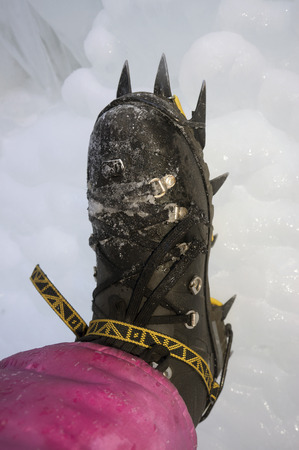 traction: Good athlete provides the right equipment Safety and comfort on difficult areas of the mountain route in the cold winter mountains in the background and beautiful wildlife
