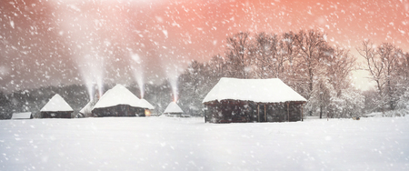 pout: After sunset, the traditional Ukrainian village began snowfall and blizzards, snowdrifts pout and covered the roads and footpaths. Thick forest and gardens beautiful pattern on the background of sky Stock Photo
