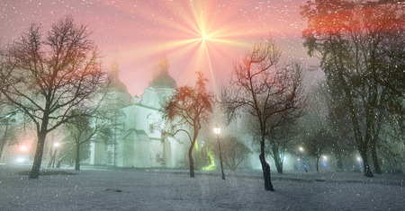 rus: Sophia Winter evening night shot of the ancient temple of Kievan Rus during a snowfall fog, among the trees of the old monastery garden and park in front of illumination during Christmas and New Year Stock Photo