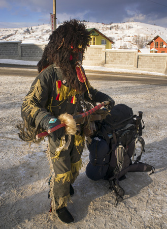 harass: Lazeyschina, Carpathian Mountains, Ukraine-January 9, 2015: Traditional folk gulyaniya- young people dress up in evil spirits and harass passers-by, this tradition is very ancient and picturesque