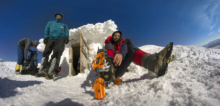 Ukraine, Vorohta- January 7, 2015: A group of athletes at an alpine refuge prepares modern equipment for training climb to the highest point Ukraine- mountain Goverla Bright sunshine and nice weather. Editorial