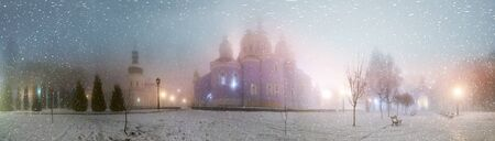 enveloped: Blizzard and rain enveloped Kiev, bad weather a bad review - a romantic mood in the old St. Michaels Cathedral, on the background of the ancient walls of the monastery and bashen- trees park and garden, beautiful illumination at night Stock Photo